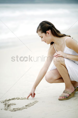 Shape : Woman drawing a heart shape on the sand