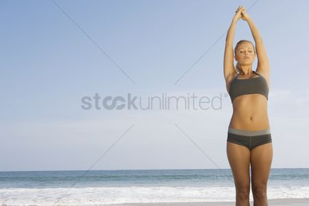 Three quarter length : Woman exercising at beach