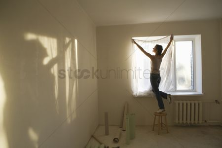 Wallpaper : Woman fitting curtains in new apartment