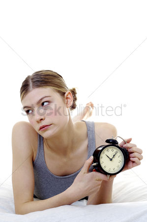 Frowning : Woman getting frustrated with her alarm clock