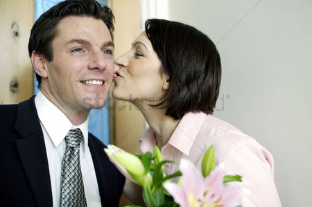 Kissing : Woman giving her husband a peck on the cheek