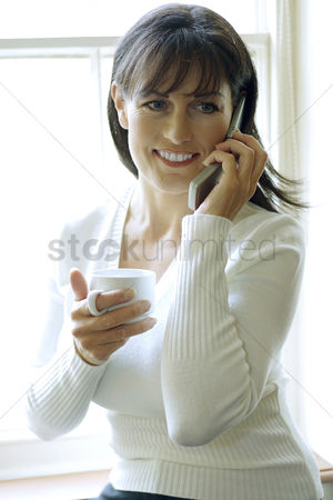 Cheerful : Woman holding a cup while talking on the phone