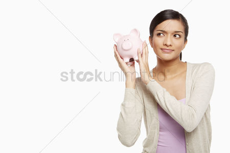Frowning : Woman holding a piggy bank