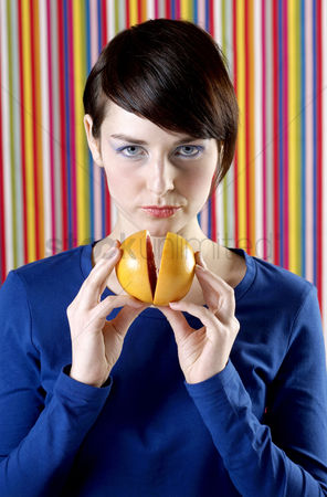 Composed : Woman holding orange