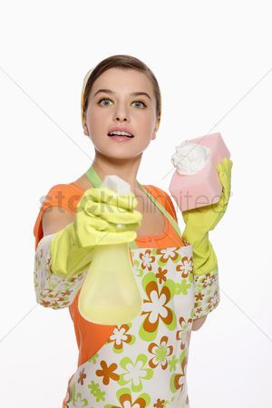 Housewife : Woman in apron holding spray bottle and cleaning sponge