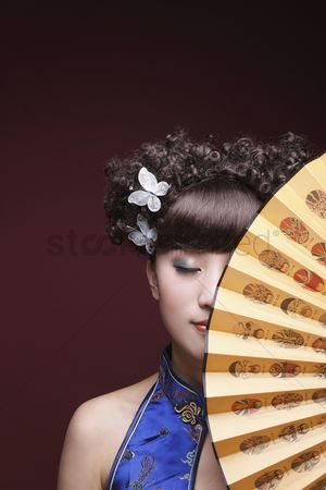 Traditional clothing : Woman in cheongsam covering part of her face with fan  eyes closed