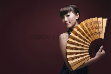 Traditional clothing : Woman in cheongsam posing with fan