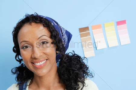 Arts : Woman in front of paint colour samples on interior wall close-up portrait