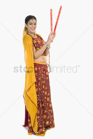 Dance : Woman in lehenga choli holding dandiya sticks