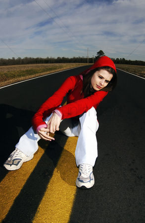 Attraction : Woman in red hooded jacket sitting in the middle of the road
