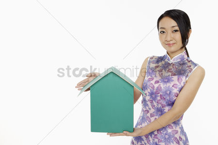 Traditional clothing : Woman in traditional clothing holding up a cardboard house