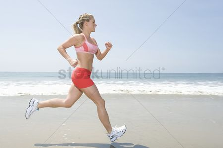 Appearance : Woman jogging along beach