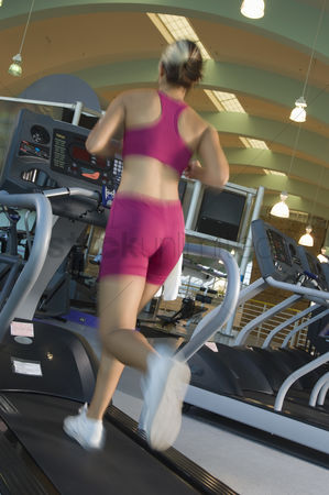 Physical : Woman jogging on treadmill at gym