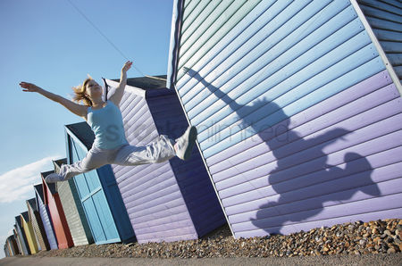 Spirit : Woman jumping in front of beach huts