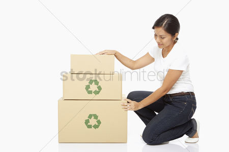 Bidayuh ethnicity : Woman kneeling beside a stack of cardboard boxes