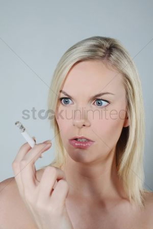 British ethnicity : Woman looking at cigarette while smoking
