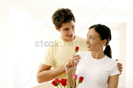 Relationship : Woman looking at her boyfriend while holding a rose