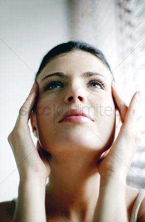 Attraction : Woman looking up while massaging her head