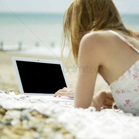 Mature : Woman lying forward on the beach using laptop