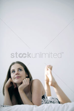 Lying forward : Woman lying forward on the bed daydreaming