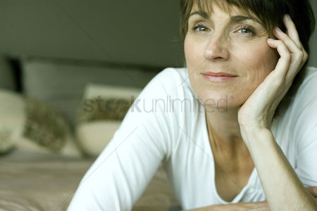 Relaxing : Woman lying forward on the bed smiling at the camera