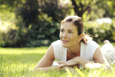 Thought : Woman lying forward on the field smiling
