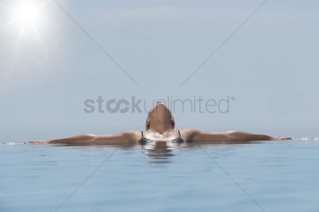 Relaxing : Woman lying head back sunbathing in pool
