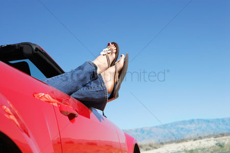 Denim : Woman lying in red convertible on desert road low section