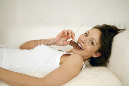 Appetite : Woman lying on the couch eating chocolate bar
