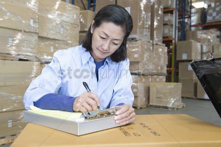 Notepad : Woman making notes in distribution warehouse