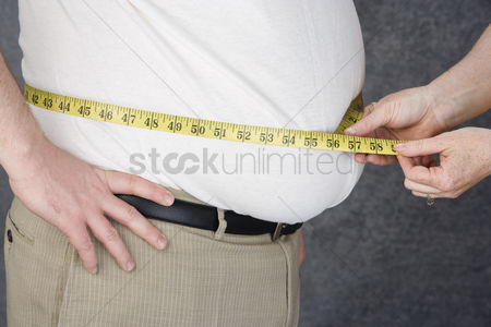 One man only : Woman measuring waist of overweight  man with tape measure middle section