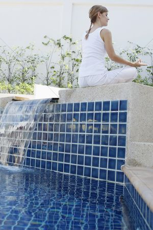 Practising yoga : Woman meditating by the pool side