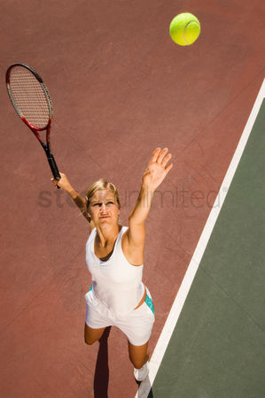 Arm raised : Woman on tennis court serving tennis ball elevated view