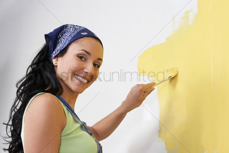 Paint brush : Woman painting interior wall low-angle view portrait