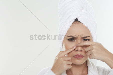 Frowning : Woman pinching pimple on her face