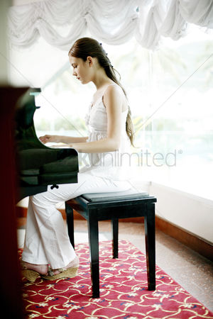 Learning : Woman playing piano at home