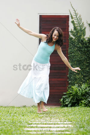 Mature : Woman playing with paving stones in a garden