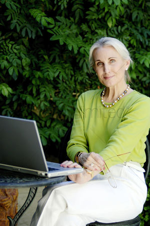 Smiling : Woman posing with a laptop on the table