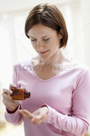 Medication : Woman pouring pills in hand