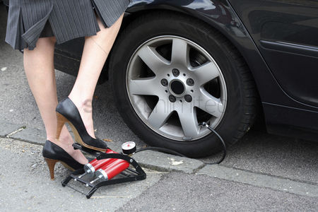 Transportation : Woman pumping a flat tire