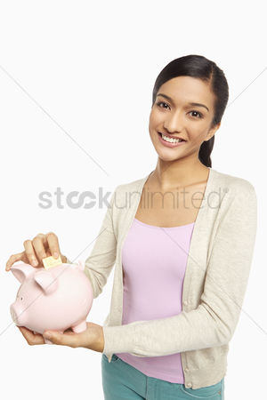 Malaysian indian : Woman putting money into the piggy bank