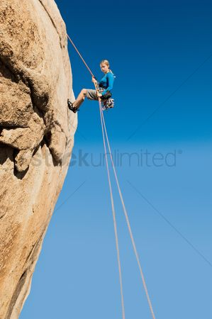 Rope : Woman rappelling on cliff side view