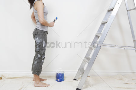 Ponytail : Woman ready to paint wall low section