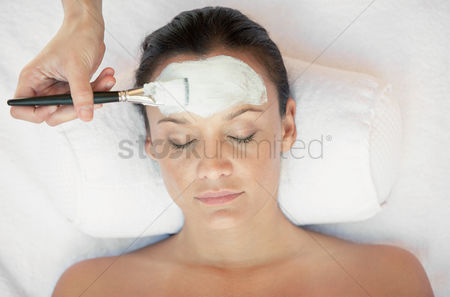 Paint brush : Woman receiving a mud therapy head and shoulders