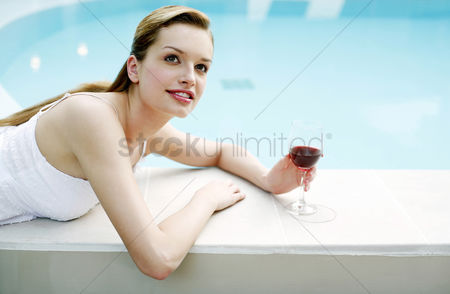Lying forward : Woman relaxing by the pool side drinking red wine