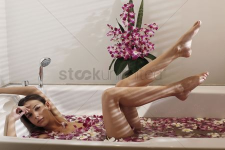Refreshment : Woman relaxing in bathtub with flower petals  raising legs