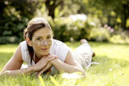 Lying forward : Woman relaxing in the park