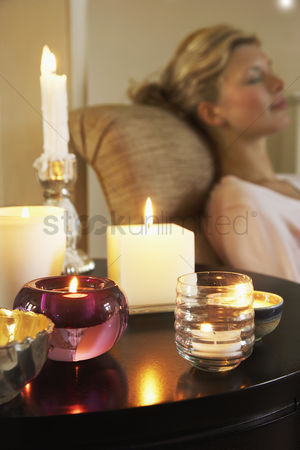 Variety : Woman relaxing on sofa beside table with candles
