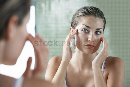 Body : Woman rubbing temples in front of mirror