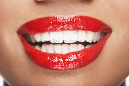 Glossy : Woman s teeth and mouth with red lipstick
